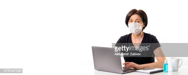 a mature woman in a medical mask works at a laptop. next to a mug of coffee or tea, hand sanitizer. - 西シベリア ストックフォトと画像
