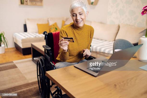 mature woman in a wheelchair working from home and shopping online - wheelchair stock pictures, royalty-free photos & images