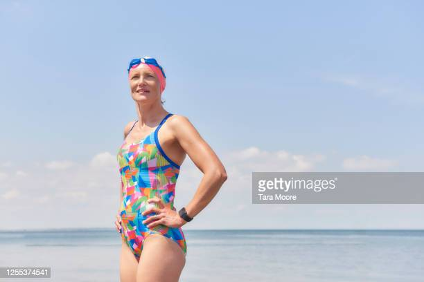 mature woman in bathing suit looking out to sea - swimming stock pictures, royalty-free photos & images
