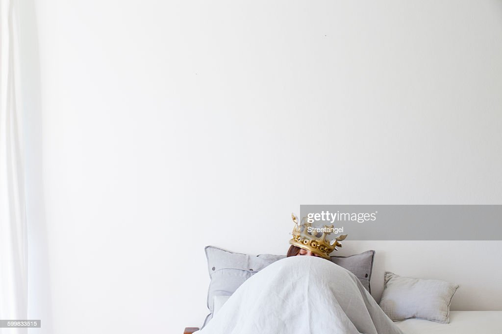 Mature woman in bed underneath quilt wearing golden crown : Stock Photo