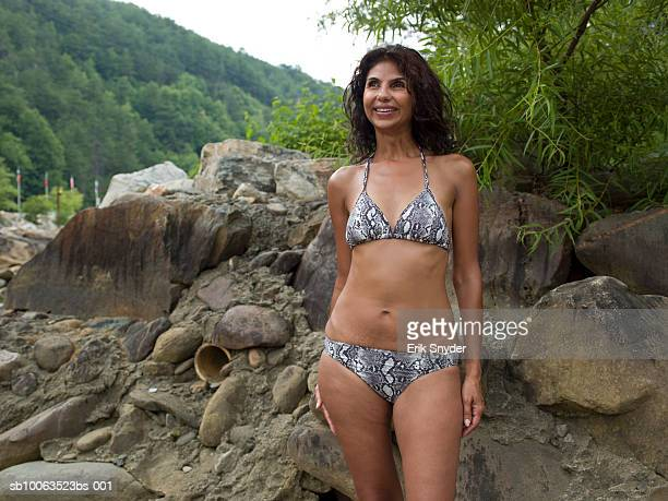 mature woman in bikini posing by rocks,smiling - indian bikini stock pictures, royalty-free photos & images