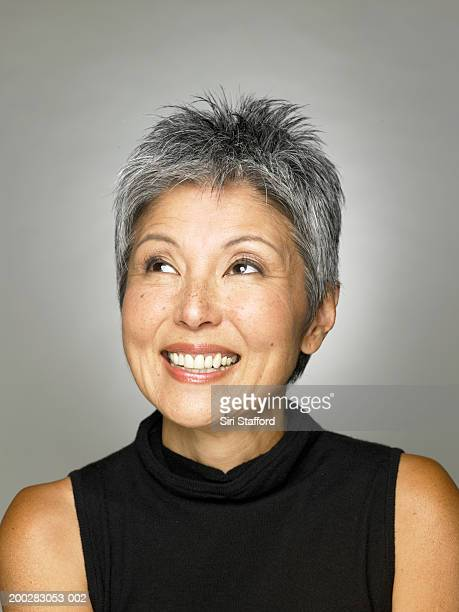 mature woman in black top looking up - asian 50 to 55 years old woman stock photos and pictures