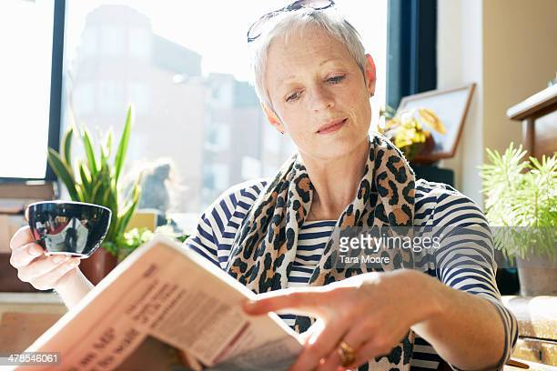 mature woman in cafe reading newspaper - news not politics stock pictures, royalty-free photos & images