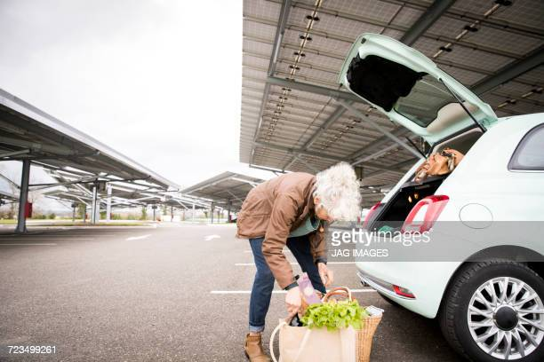 mature woman in car park, loading shopping into boot of car - car trunk stock pictures, royalty-free photos & images