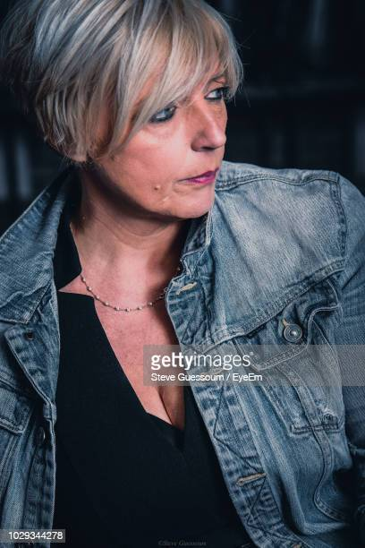 mature woman in denim jacket looking away - steve guessoum stockfoto's en -beelden