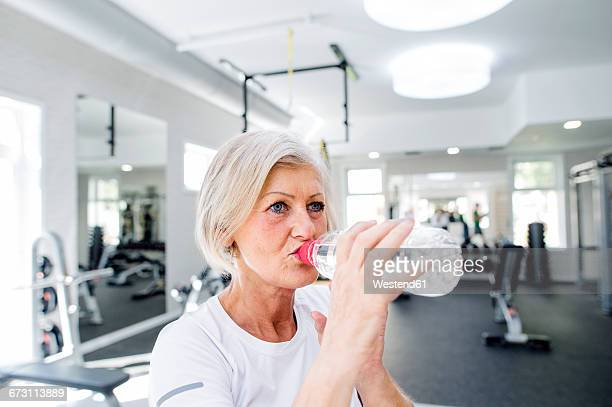 Mature woman in fitness gym drinking water from bottle