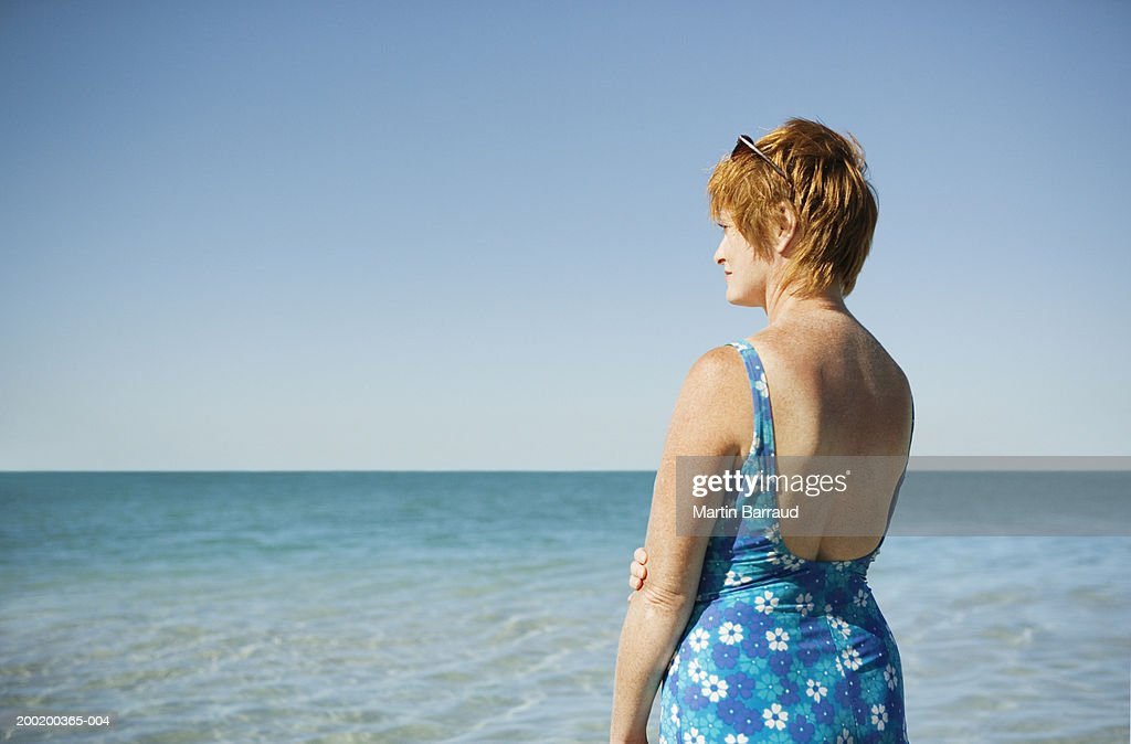 Mature Woman In Floral Swimming Costume Standing By Sea Rear View