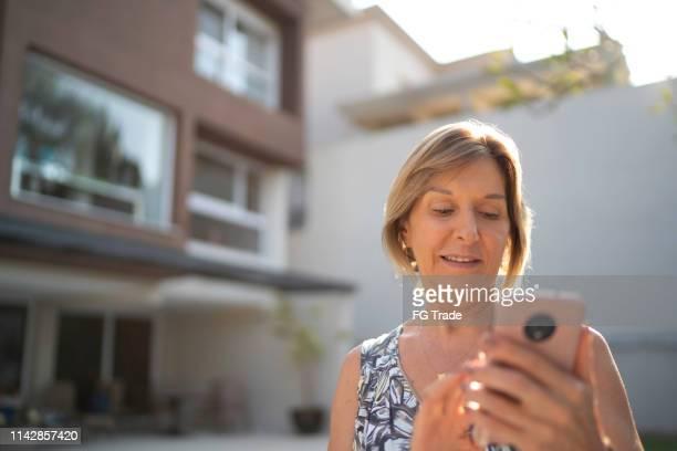 oudere vrouw in de voorkant van een huis met behulp van mobiele - voor of achtertuin stockfoto's en -beelden