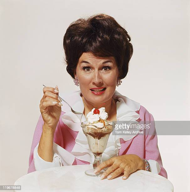 Mature woman in front of sundae against white background, close-up