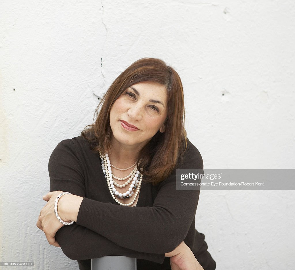 Mature woman in front of wall outdoors, portrait : Stock Photo