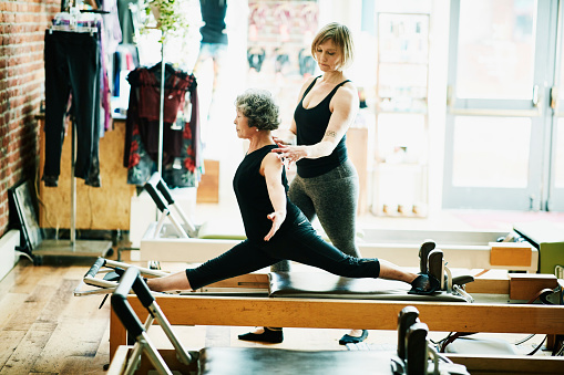 Mature woman in front split on pilates reformer during class while female trainer adjusts form - gettyimageskorea
