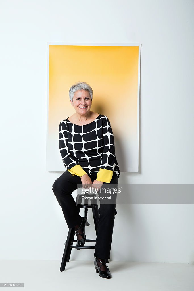 Mature woman in funky dress and yellow background : Stock-Foto