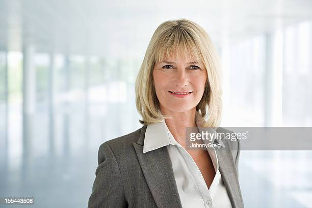 Mature woman in gray business suit smiling