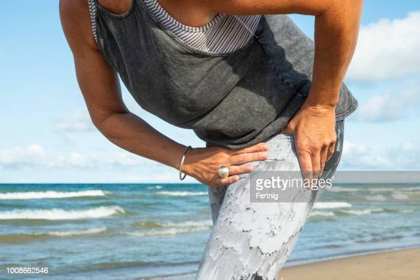 a mature woman in her fifties experience hip pain during a morning run - pain stock pictures, royalty-free photos & images