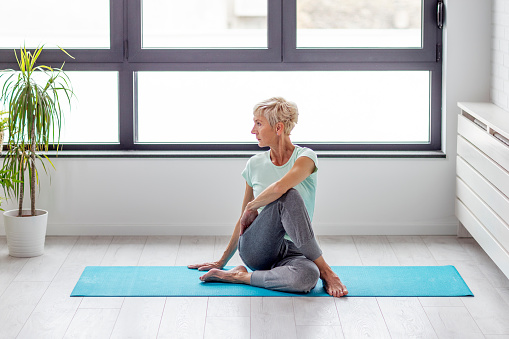 Mature woman in joga pose exercise in appartment at rug with window on background 1090022444