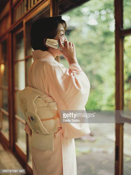 Mature woman in kimono using mobile phone, side view