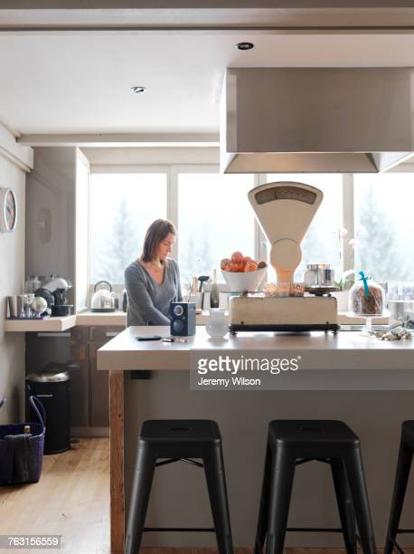 Mature woman in kitchen, pensive expression