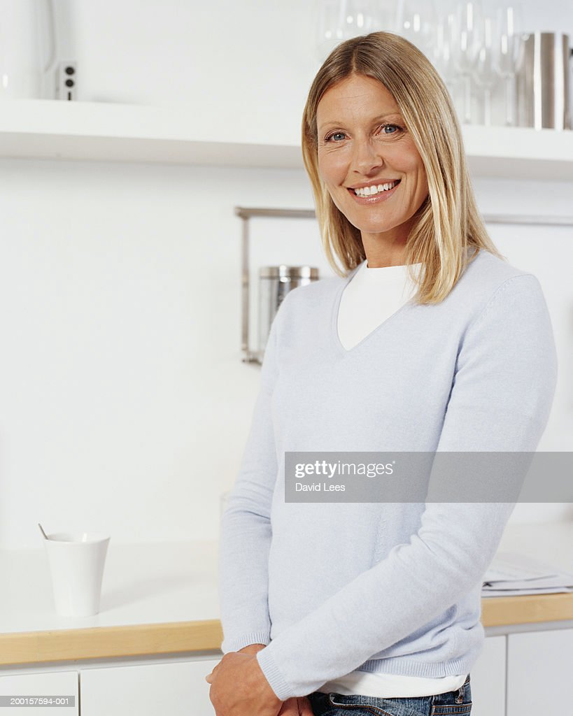 Mature Woman In Kitchen Smiling Portrait Stock Photo | Getty Images