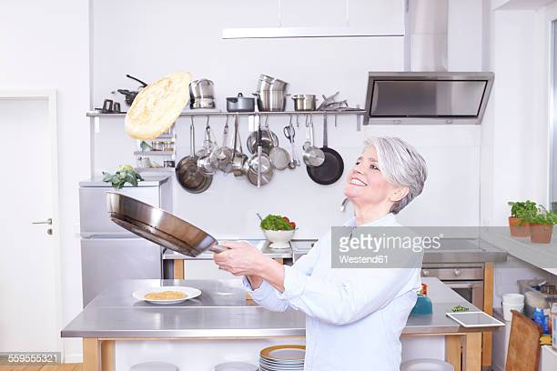 Mature woman in kitchen throwing up pancake in pan