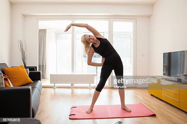 mature woman in lounge standing on yoga mat bending over sideways arm raised stretching - older woman bending over stock pictures, royalty-free photos & images