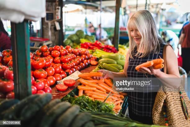 mature woman in market shopping vegetables - bancarella di verdura foto e immagini stock