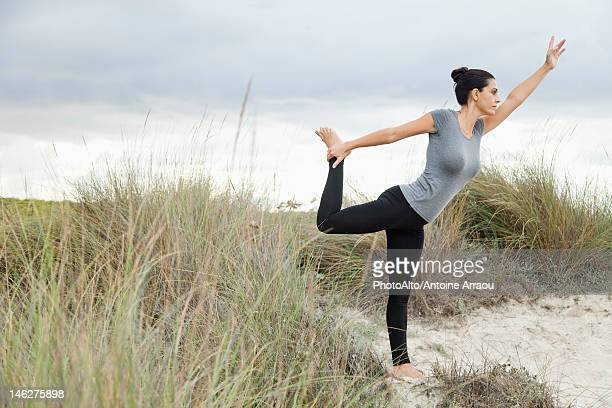 Mature woman in Natarajasana pose on beach, side view