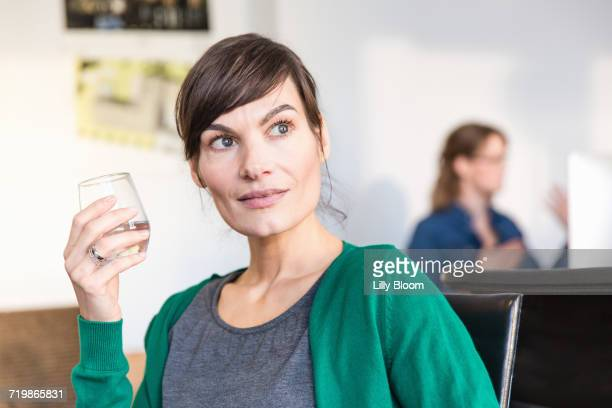 Mature woman in office holding drinking glass looking away