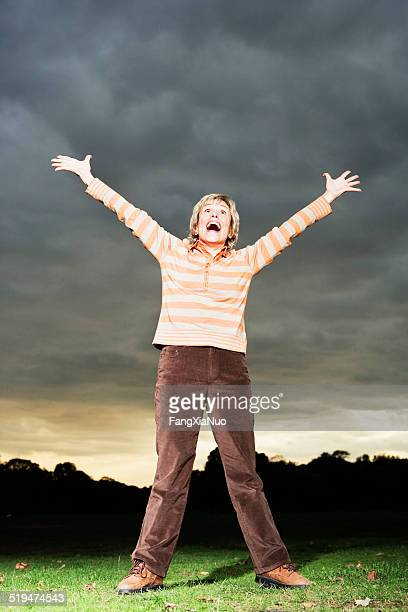 mature woman in park with arms stretched out, mouth open - legs spread open stock photos and pictures