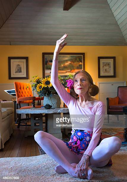 mature woman in pink leotard stretches - leotard and tights stock photos and pictures