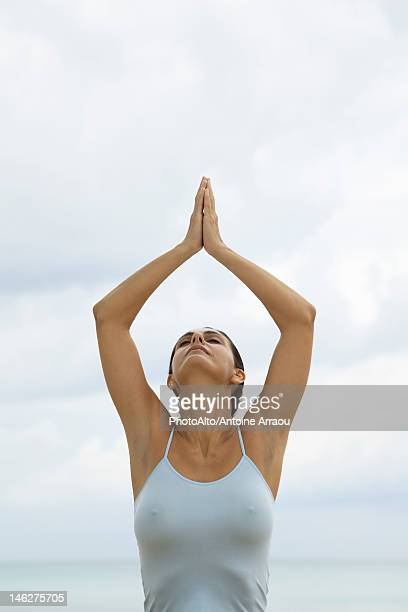 Mature woman in prayer position with arms above head