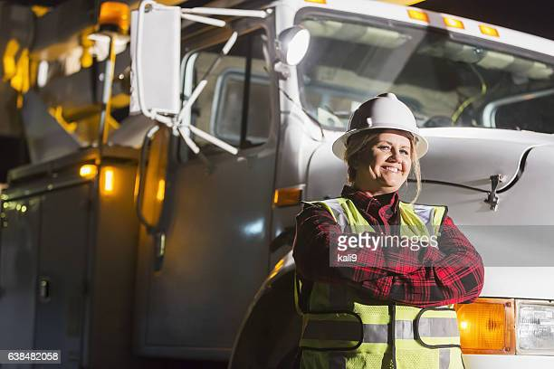 Mature woman in safety vest, hardhat with truck