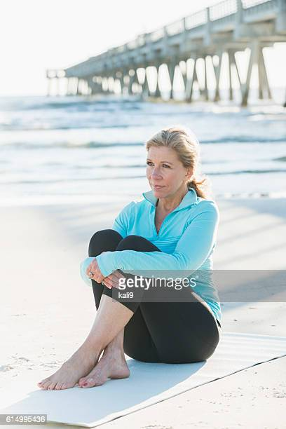 Mature woman in sports clothing sitting on beach