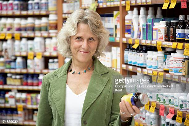 "mature woman in store, holding bottle, portrait - ""compassionate eye"" fotografías e imágenes de stock"