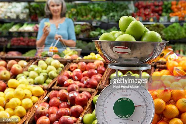 'Mature woman in supermarket, focus on weighing scale'