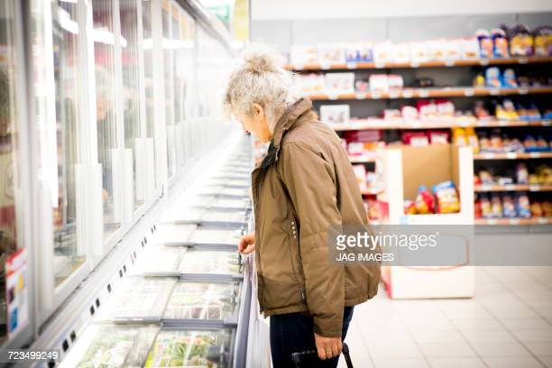 mature woman in supermarket, looking in freezer cabinet - frozen food stock pictures, royalty-free photos & images