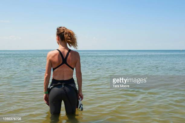 mature woman in swimwear looking out to sea - back stock pictures, royalty-free photos & images