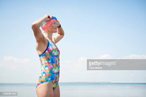 mature woman in swimwear looking out to sea - multi coloured stock pictures, royalty-free photos & images