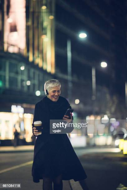 Mature woman in the city by night.