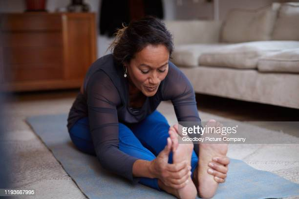 mature woman in the seated forward bend pose at home - good posture stock pictures, royalty-free photos & images