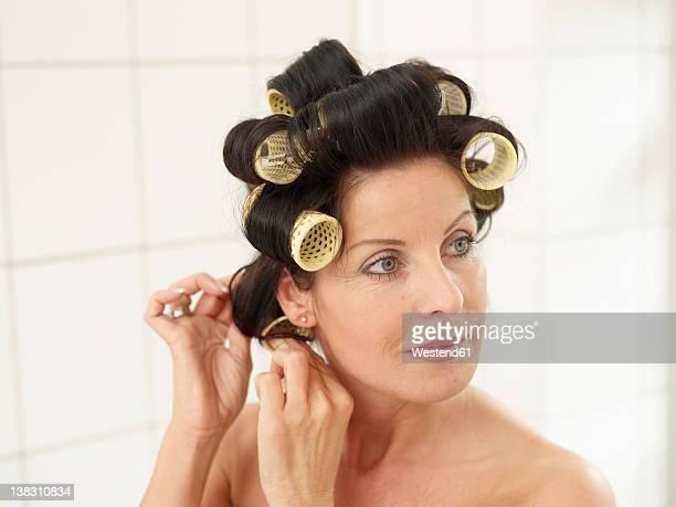 mature woman in towel with hair rollers, smiling - krulspelden stockfoto's en -beelden