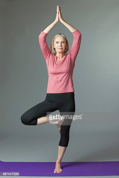 Mature woman in 'tree' yoga position