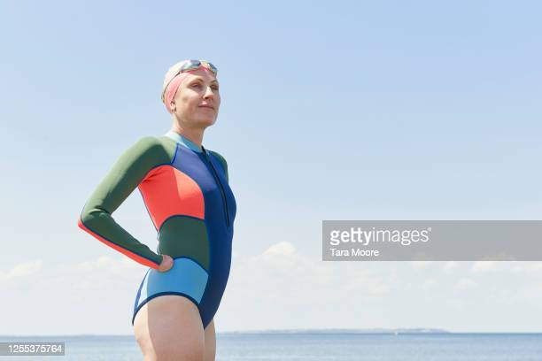 mature woman in wetsuit looking out to sea - disability stock pictures, royalty-free photos & images