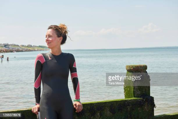 mature woman in wetsuit looking out to sea - england stock pictures, royalty-free photos & images