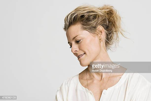 Mature woman in white shirt looking down