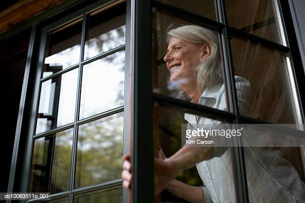 Mature woman in window, smiling, low angle view