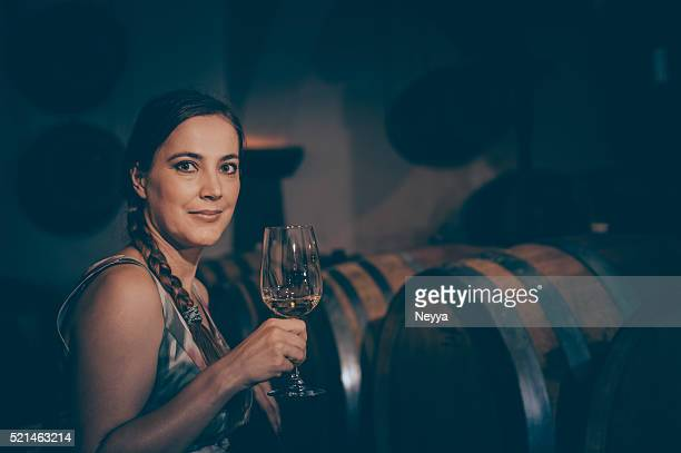 Mature Woman in Winery Cellar with Glass of White Wine