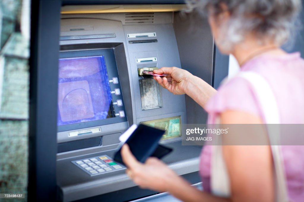 Mature woman inserting credit card into local french cash machine : Stock Photo