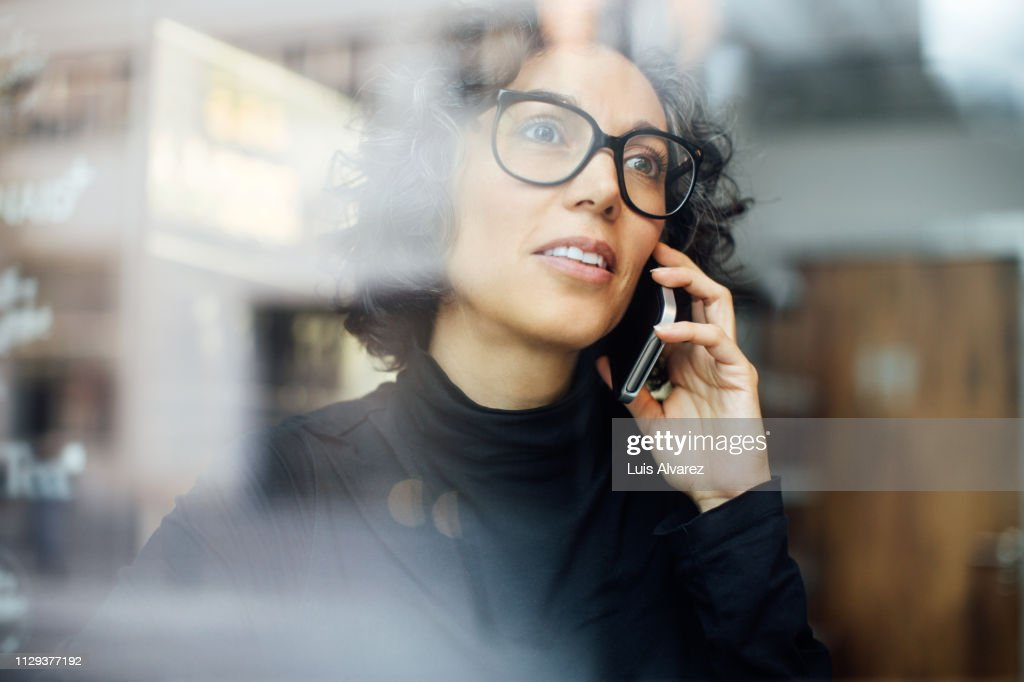 Mature woman inside a cafe talking on mobile phone : Stock Photo