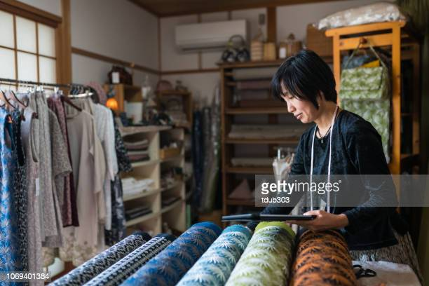 mature woman inspecting the finished textile fabric she designed after manufacturing - textile industry stock pictures, royalty-free photos & images