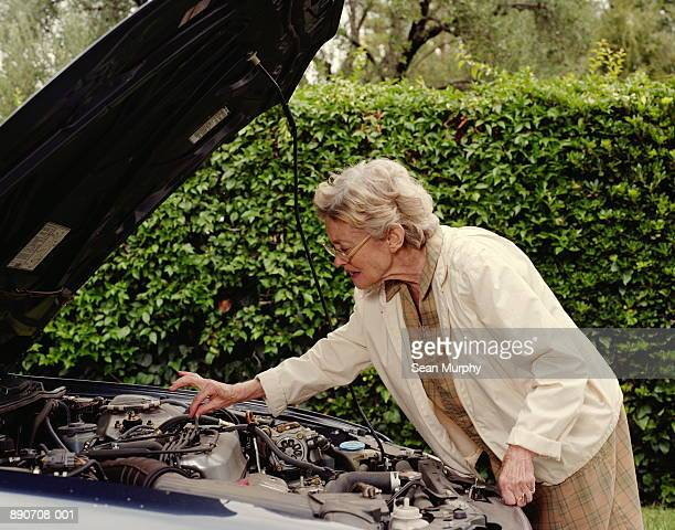 mature woman inspecting wiring under hood of car - inconvenience stock pictures, royalty-free photos & images